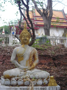 Buddha image in front of an old monastic structure